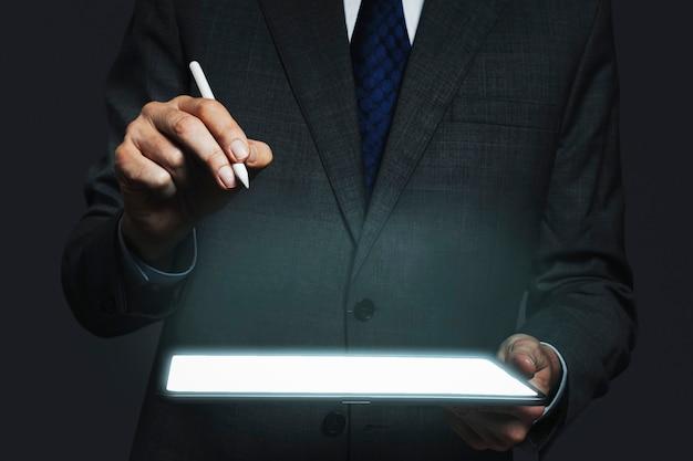 Hombre de negocios que presenta holograma invisible que se proyecta desde la tecnología avanzada de la tableta