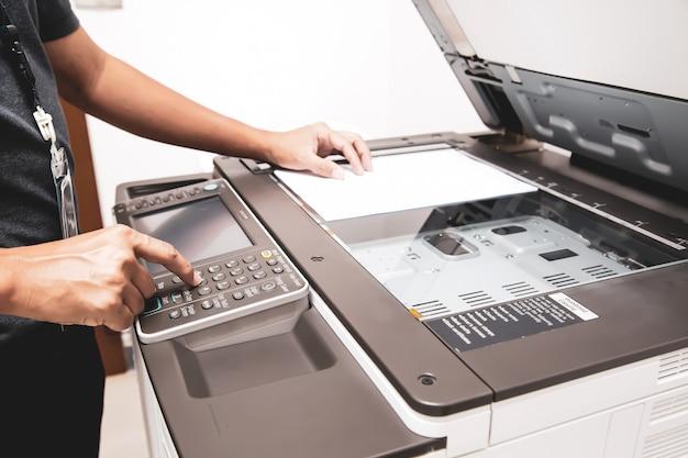 El hombre de negocios que presiona el botón con la fotocopiadora o la impresora es un equipo de herramientas de oficina para escanear documentos y copiar papel.