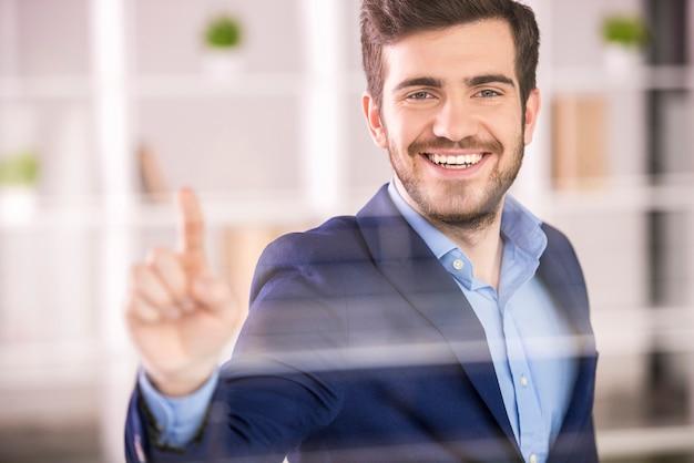 Hombre de negocios que presiona en la pantalla de cristal en oficina.