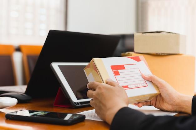 Hombre de negocios que recibe la caja de cartón de paecel con la tableta y labtop en la tabla.