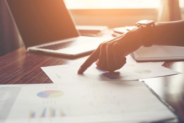 El hombre de negocios que señala el dedo análisis de las estadísticas financieras gráfico