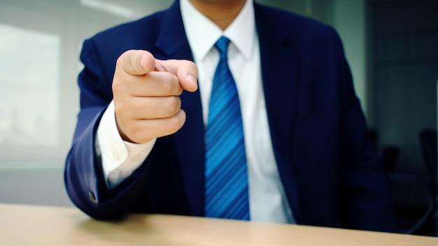 Hombre de negocios que señala el dedo en usted en el escritorio