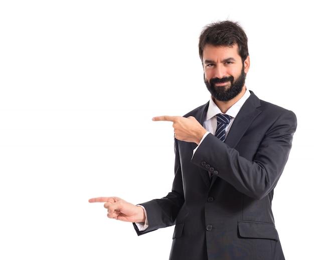 Hombre de negocios que señala a la lateral sobre fondo blanco