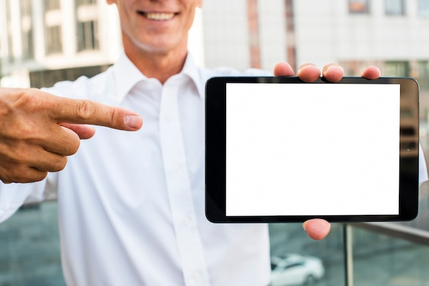 Hombre de negocios que señala en la maqueta de la tableta
