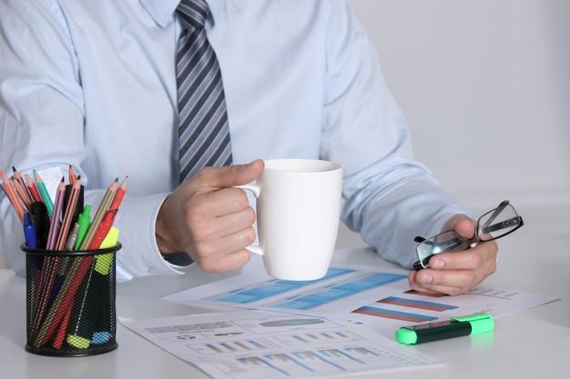 Hombre de negocios que se sienta en el escritorio de oficina que tiene un descanso para tomar café