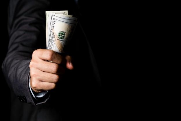 Hombre de negocios que sostiene el billete de banco del dólar de ee. uu. en fondo negro. usd es la moneda de cambio principal en el mundo.