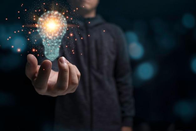 Hombre de negocios que sostiene la bombilla virtual que brilla intensamente con la luz anaranjada. nuevo concepto creativo de idea de negocio.