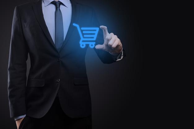 Hombre de negocios que sostiene el carro mini carro de la compra en la interfaz de pago digital empresarial. concepto de negocio, comercio y compras.