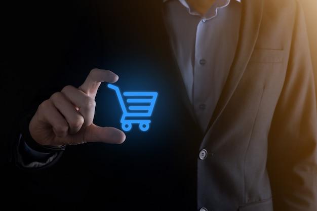 Hombre de negocios que sostiene el carro mini carro de la compra en la interfaz de pago digital empresarial