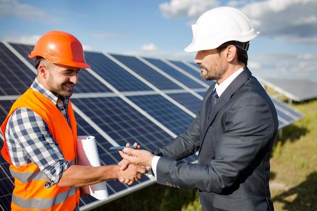 Hombre de negocios que sostiene el detalle fotovoltaico y que sacude la mano a un capataz.