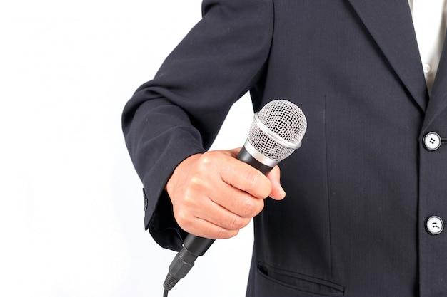 Hombre de negocios que sostiene un micrófono aislado en el fondo blanco