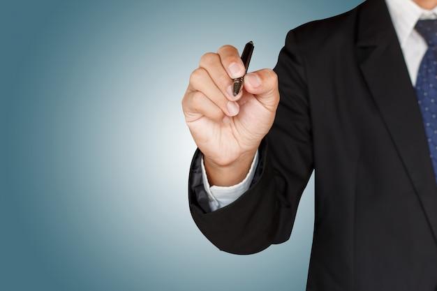 Hombre de negocios que sostiene una pluma en fondo verde