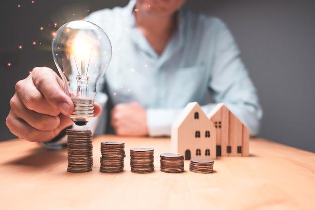 Hombre de negocios que sostiene y que pone la bombilla al apilamiento de las monedas. la nueva idea creativa de negocio puede generar ganancias con el concepto de dinero.