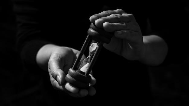 Hombre de negocios que sostiene un reloj de arena de madera clásico en la oscuridad. concepto de ideas de pensamiento y control de tiempo.
