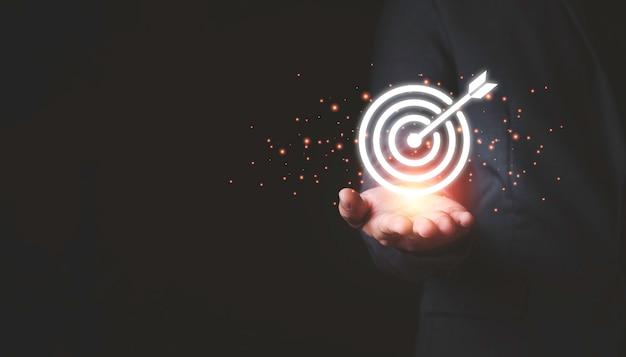 Hombre de negocios que sostiene el tablero de dardos virtual y la flecha con espacio de la copia para el concepto del objetivo del objetivo del negocio de la configuración.