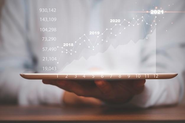 Hombre de negocios que sostiene la tableta con el gráfico y el gráfico del mercado de valores, análisis del inversor de valor para el concepto comercial.