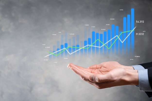 Hombre de negocios que sostiene la tableta y que muestra gráficos holográficos y estadísticas del mercado de valores obtiene ganancias.