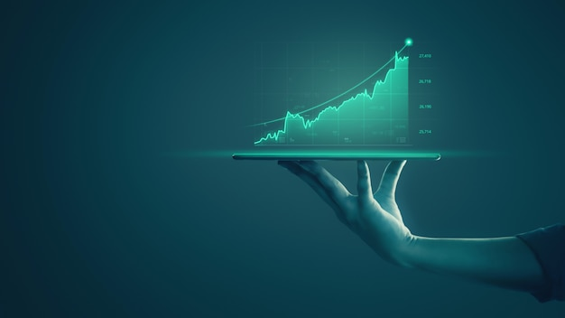 El hombre de negocios que sostiene la tableta y que muestra gráficos holográficos y estadísticas del mercado de valores obtiene ganancias.