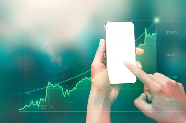 El hombre de negocios que sostiene el teléfono inteligente y muestra gráficos holográficos y estadísticas del mercado de valores obtiene ganancias.