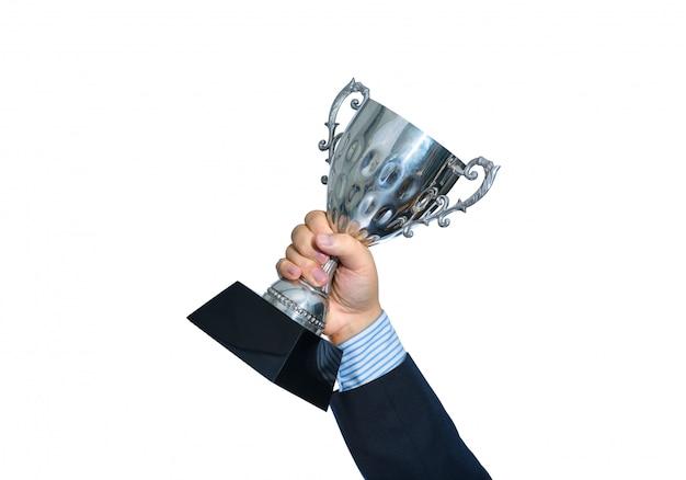 Hombre de negocios que sostiene un trofeo de plata del campeón en el fondo blanco
