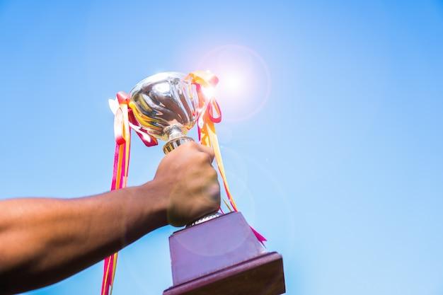 Hombre de negocios que tiene el trofeo del premio de oro con la victoria de mostrar la cinta para el premio al mejor logro de éxito