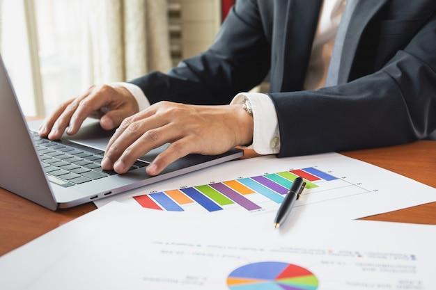 Hombre de negocios que trabaja con la computadora portátil con la carta común del gráfico en el trabajo de la tabla del concepto casero.