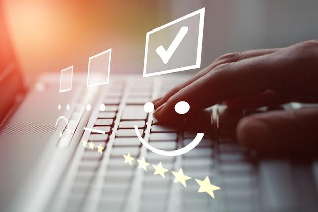 Hombre de negocios que trabaja en la computadora portátil del teclado con el concepto de la evaluación del servicio al cliente.