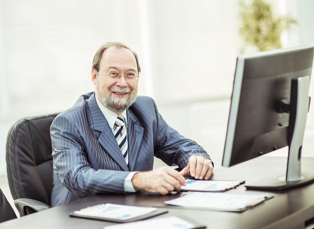 Hombre de negocios que trabaja con gráficos financieros en el lugar de trabajo.
