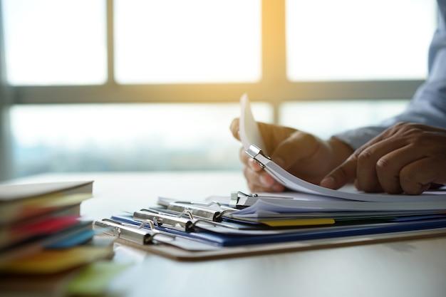 El hombre de negocios que trabaja leyendo los documentos financieros del gráfico al éxito del trabajo analiza los planes del documento