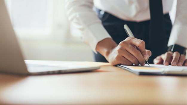Hombre de negocios que trabaja en la oficina con firmar un documento y una computadora portátil. concepto de negocio moderno.