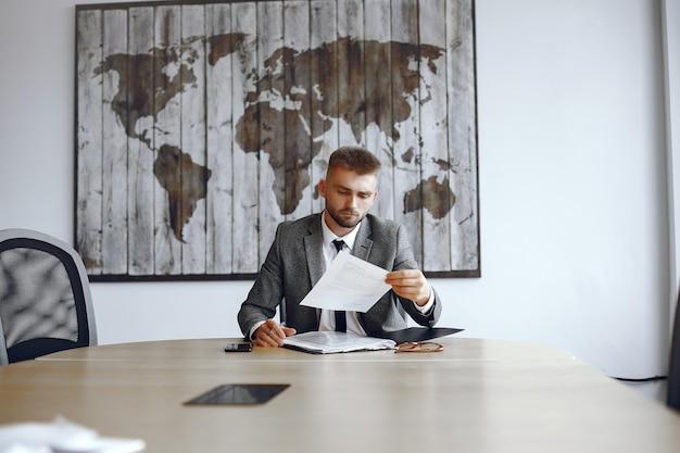 Hombre de negocios que trabaja en la oficina. el hombre lee los contratos. chico está sentado en la oficina
