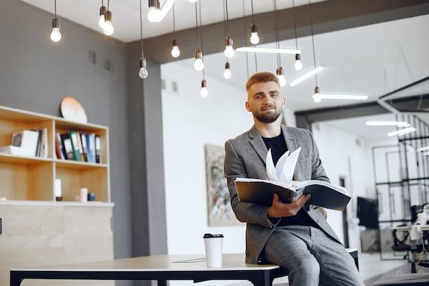 Hombre de negocios que trabaja en la oficina. el hombre sostiene una carpeta. chico está sentado en la oficina