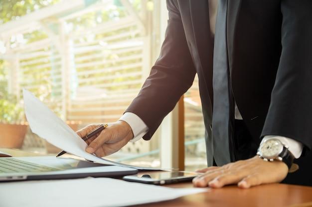 Hombre de negocios que trabaja en su oficina con el papeleo de los documentos.