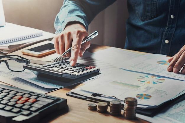 Hombre de negocios que usa la calculadora con la pluma de tenencia de la mano que trabaja en oficina.