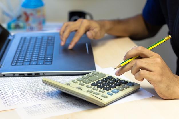 Hombre de negocios que usa la computadora portátil de la calculadora y de la computadora para calcular finanzas en la tabla del escritorio apagado