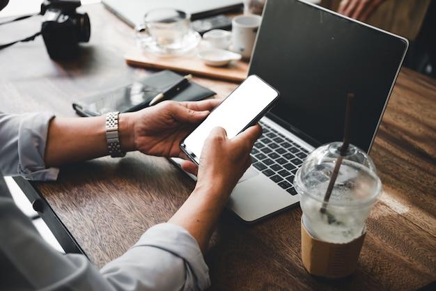 El hombre de negocios que usa el móvil y la computadora portátil encuentran un trabajo en cafetería