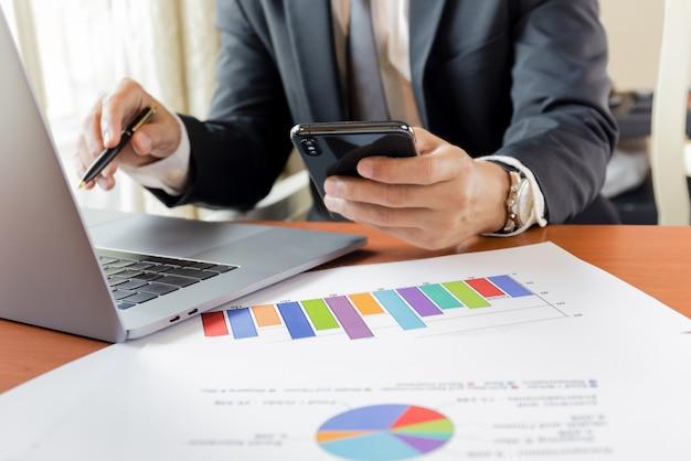 El hombre de negocios que usa en el teléfono celular con el ordenador portátil y las cartas gráficos papel en la mesa de trabajo desde casa.