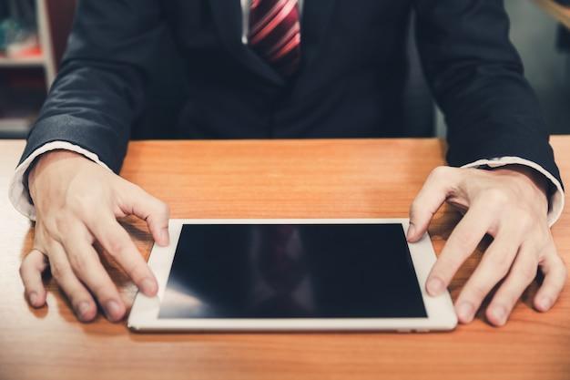 Hombre de negocios que usa el teléfono inteligente y la computadora portátil
