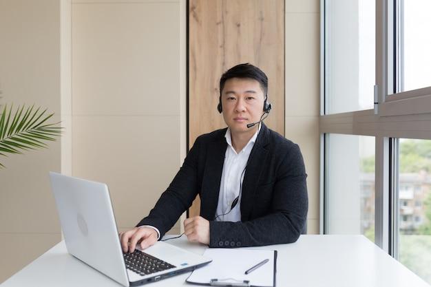 Hombre de negocios realiza formación en línea utilizando un auricular y una computadora portátil