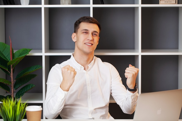 Hombre de negocios relajado que trabaja con una computadora portátil en su oficina.