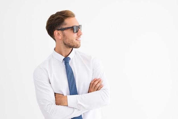 Hombre de negocios relajado usando gafas de sol y mirando a otro lado