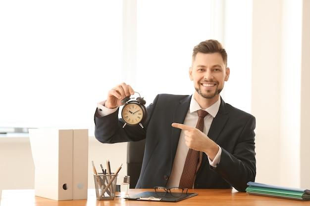 Hombre de negocios con reloj despertador en la mesa de la oficina.