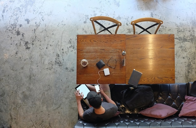 Hombre de negocios en ropa casual sentarse a la mesa con una tableta en sus manos y utiliza un teléfono inteligente en un café en sus manos. por encima de la vista.