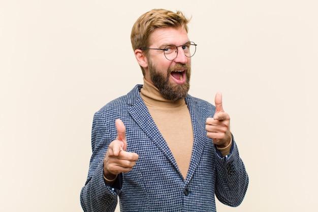 Hombre de negocios rubio joven que sonríe con una actitud positiva, acertada, feliz que señala, haciendo la muestra del arma con las manos