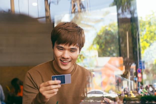 Hombre de negocios seguro de compras en línea con tarjeta de crédito usando la computadora portátil en el café