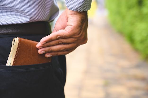 Hombre de negocios seguro manteniendo la billetera de dinero en el bolsillo trasero.