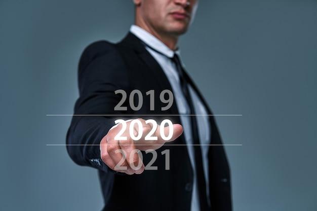 El hombre de negocios selecciona el año 2020 en el menú virtual, busca datos, historial comercial sobre fondo gris.