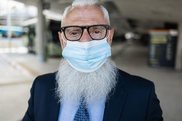 Hombre de negocios senior en la ciudad con mascarilla de seguridad para el brote de coronavirus