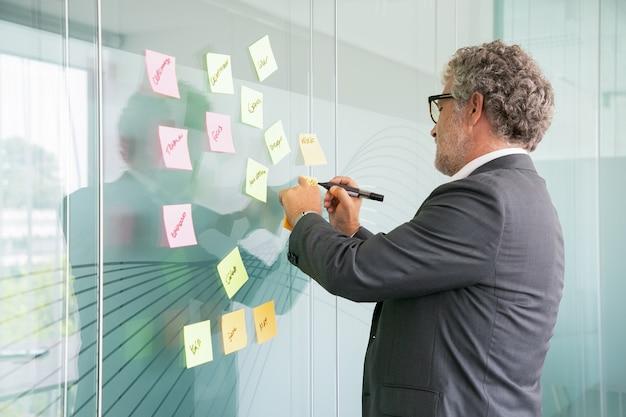Hombre de negocios senior concentrado escribiendo en etiqueta con marcador negro