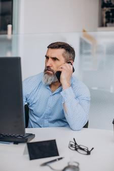 Hombre de negocios senior guapo trabajando en la computadora en la oficina
